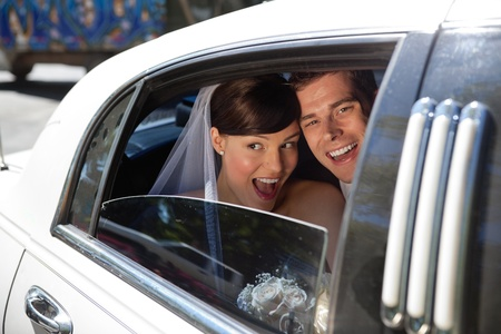 Newly weds laughing in car photo