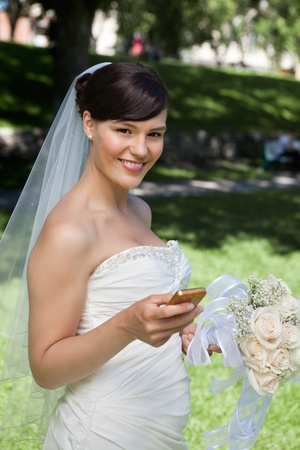 Portrait of smiling newlywed bride holding cell phone photo