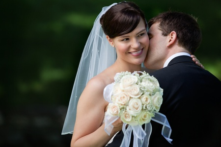 Joven novio besando en la mejilla hermosa novia