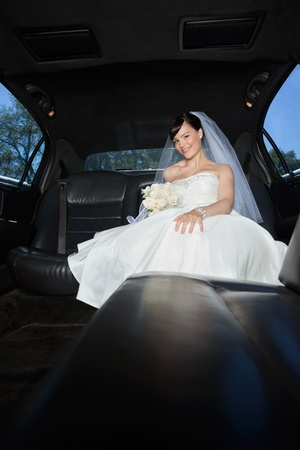 Beautiful bride sitting in limousine holding flower bouquet photo