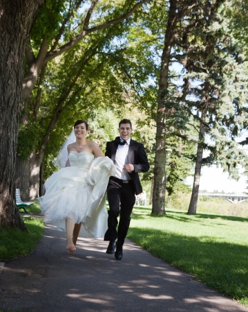 Happy bride and groom running along the walkway photo