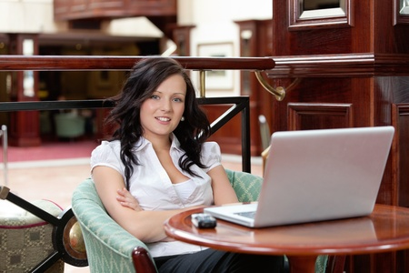 Portrait of casual female sitting with arms crossed, laptop and cell phone on table photo