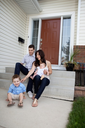 Happy family sitting on steps in front of house Stock Photo - 11702295