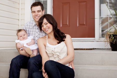 outside of house: Portrait of a husband and wife with small baby child