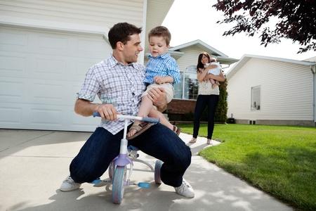 papa y mama: Padre juguet�n sentado en triciclo con su hijo mientras que la esposa de pie en el fondo de la hija