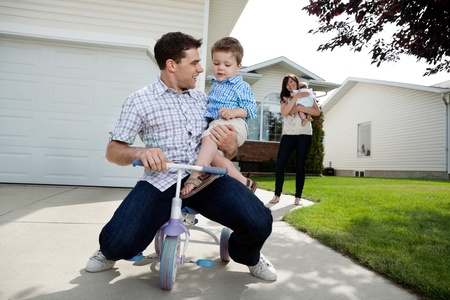 tricycle: Playful father sitting on tricycle with son while wife standing in background with daughter