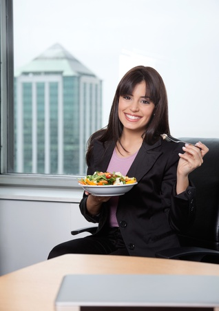 Portrait of business woman having fresh salad of vegetables photo
