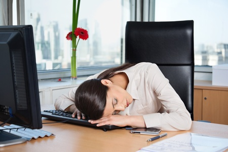 Tired business woman sleeping on the keyboard in office photo