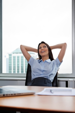 Pretty businesswoman sitting on office chair and relaxing with hands behind head photo