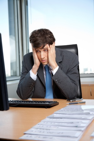 worked: Stressed out businessman sitting at his desk in front of computer Stock Photo