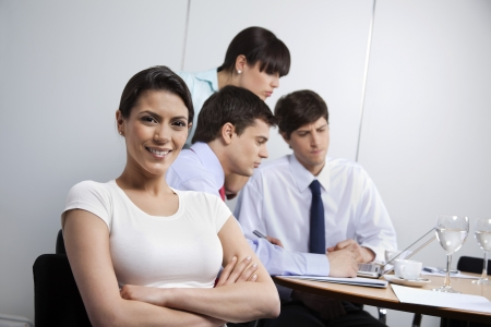 Portrait of pretty businesswoman smiling while colleagues working in background photo
