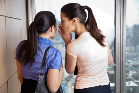 old office: Two female co-workers whispering in office