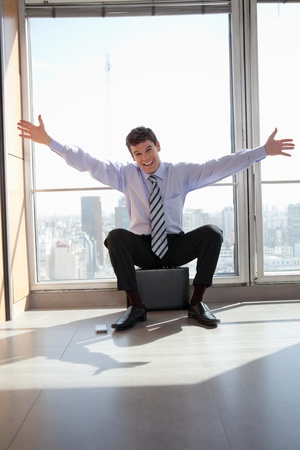 relieved: Portrait of excited male entrepreneur sitting on briefcase