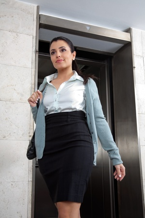 people in elevator: Low angle view of confident female entrepreneur stepping out of elevator