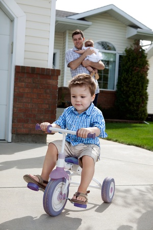 Toddler boy learning to ride tricycle with father in background photo