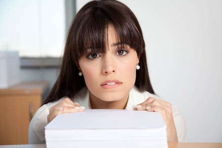 Portrait of overstrained woman at her desk with pile of paperwork photo