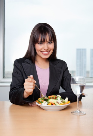 office break: Portrait of smiling businesswoman having fresh vegetable salad with glass of water on desk