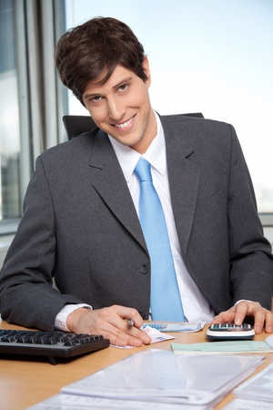 Portrait of young business man calculating budget using calculator at office photo