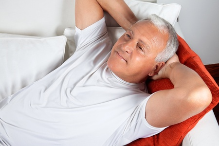 Senior man relaxing on sofa with hands behind his head photo