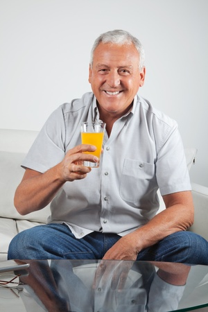 Portrait of happy senior man having glass of fresh orange juice Stock Photo - 11702339