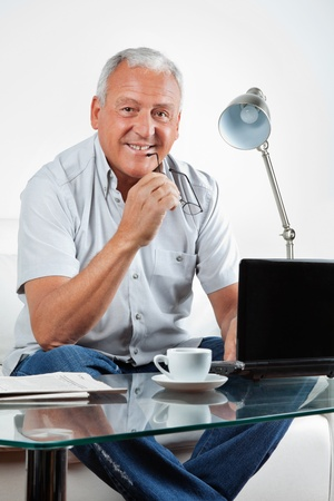 Portrait of smiling senior man sitting with laptop on table at home photo