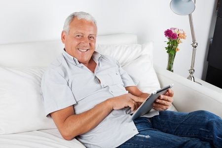 Portrait of smiling senior man using digital tablet PC photo