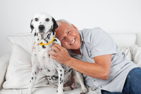 cuddly: Portrait of senior man sitting on sofa with his pet dog at home