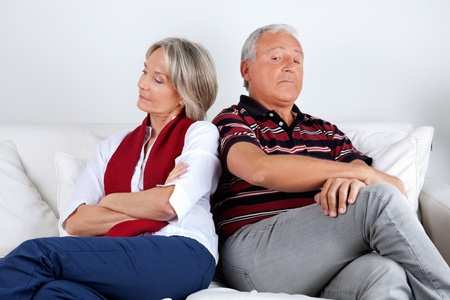 Senior couple sitting on sofa after argument photo
