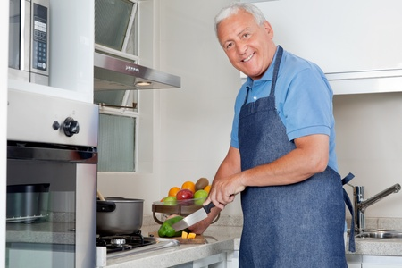 Portrait of happy senior man cutting vegetables at kitchen counter at home photo
