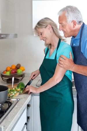 Senior couple cooking food in kitchen at home photo