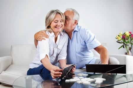 rummy: Loving husband kissing his wife while playing rummy at home.