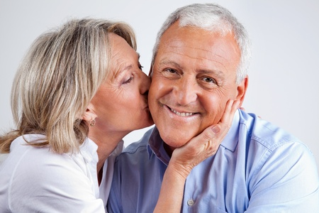 mid adult couples: Portrait of husband being kissed by his loving wife