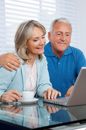Happy couple browsing internet together on laptop photo