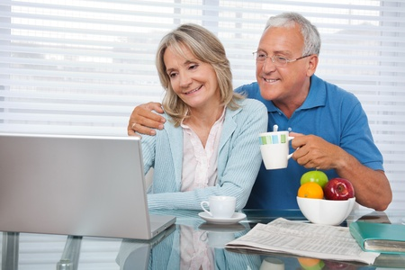 mid adult man: Happy couple using laptop while having breakfast Stock Photo