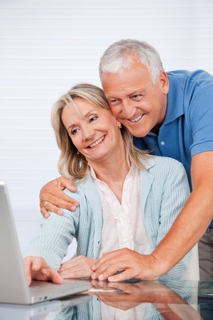 Happy couple using laptop together at home photo