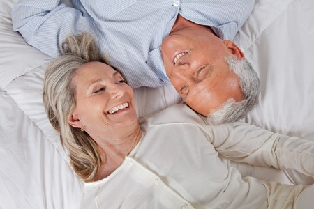 elderly couples: Top view of happy couple lying in bed Stock Photo
