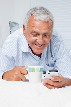old cell phone: Smiling senior man using cell phone while having tea