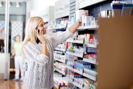 Female talking on cell phone while looking for medicines at drugstore photo