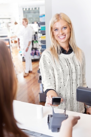 pay for: Female customer using cell phone to pay for goods