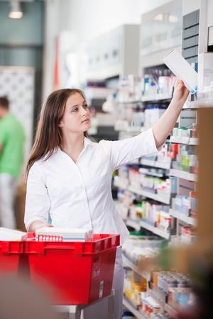 Female pharmacist keeping medicine box on the shelf at drugstore photo