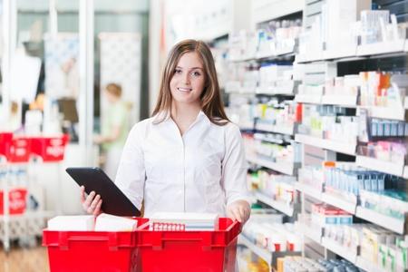 farmacia: Retrato de mujer sosteniendo qu�mico de pie Tablet PC con la cesta en la farmacia