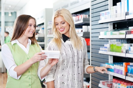 pharmacy store: Female pharmacist advising customer at pharmacy