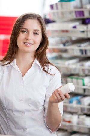 Portrait of female pharmacist holding medication container photo
