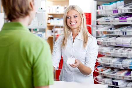 pharmacy technician: Female pharmacist giving medicine to customer at counter