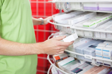 Cropped image of man holding medication box at pharmacy photo