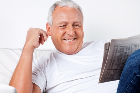 Smiling senior man reading newspaper at home photo