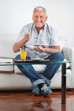 Portrait of happy senior man having breakfast photo