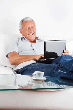 Relaxed senior man sitting on sofa working on laptop at home photo