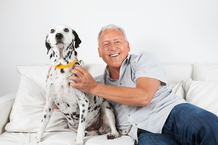 dog health: Portrait of happy casual senior man sitting with his pet dog on sofa