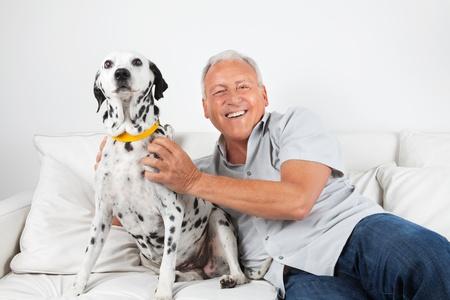 dog health: Ritratto di felice Casual Uomo anziano seduto con il suo cane sul divano Archivio Fotografico